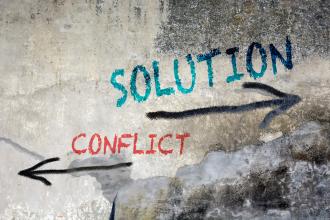 Mauersteine mit Pfeilen in zwei Richtungen: entweder Lösung oder Konflikt
