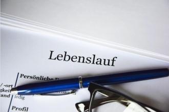 Stift und Brille liegen auf einem Papier mit der Überschrift Lebenslauf